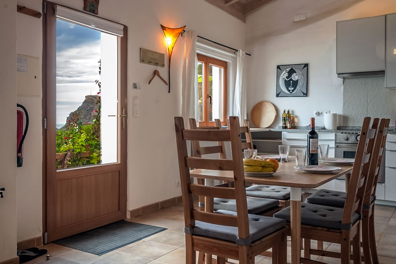 Dining table and entrance door of the holiday house in Arrifana