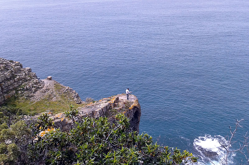 Fisherman on a cliff close to Arrifana beach