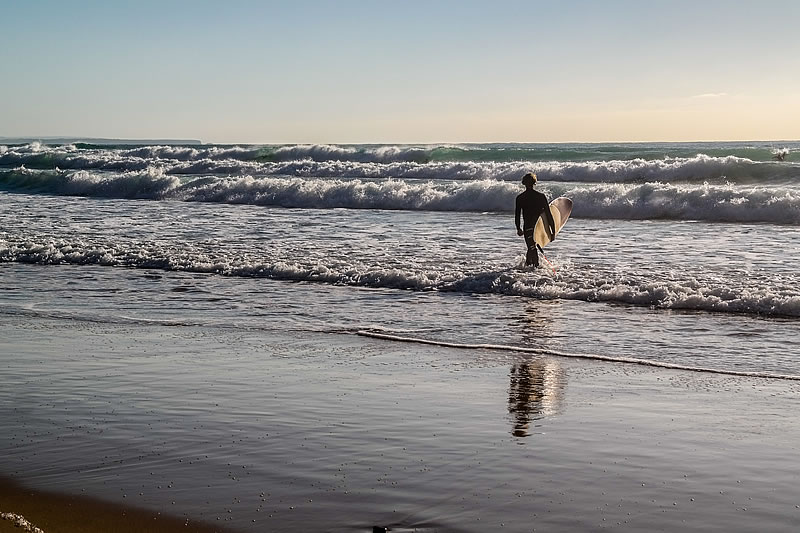 Surfer goes in the water in Arrifana beach